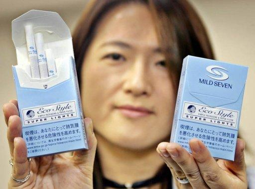 This file photo shows Japan Tobacco (JT) official displaying 'Mild Seven Super Lights Eco Style' cigarrete boxes during a press preview in Tokyo, in 2005. JT shares jumped more than seven percent in Tokyo trade on Monday after the government said it would delay selling part of its stake in the former monopoly.