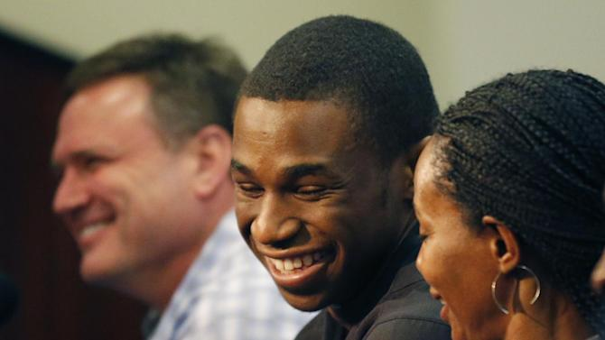 Kansas freshman NCAA college basketball player Andrew Wiggins, center, smiles with his mother Marita Payne-Wiggins, right, during of a news conference at the University of Kansas in Lawrence, Kan., Monday, March 31, 2014. Coach Bill Self, left, smiles with the standout guard. Wiggins announced he would be entering the NBA draft