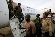 """Foreigners captured by Sudanese military in the Heglig oilfield area April 28, are escorted off an airplane in Khartoum. The British embassy was """"urgently"""" investigating on Sunday the arrest in Sudan of one of its citizens, who was among four foreigners the Sudanese military said it captured in the tense Heglig oil region"""