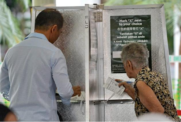 Residents in Punggol East queue at a polling station to cast their vote.