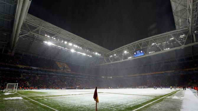 Workers clean the snow from the pitch after the Champions League match between Galatasaray and Juventus was paused for 20 minutes due heavy snowfall in Istanbul.
