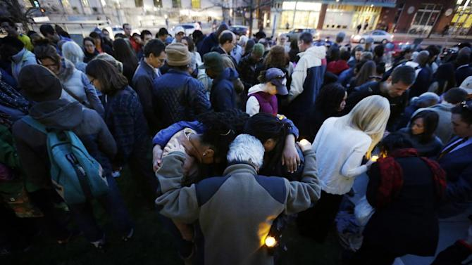 Mourners pray during a candlelight vigil in the aftermath of Monday's Boston Marathon explosions Wednesday, April 17, 2013, at City Hall in Cambridge, Mass. (AP Photo/Matt Rourke)