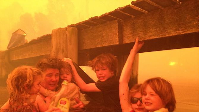 In this Jan. 4, 2013, photo provided by the Holmes family, Tammy Holmes, second from left, and her grandchildren, two-year-old Charlotte Walker, left, four-year-old Esther Walker, third from left, nine-year-old Liam Walker, eleven-year-old Matilda, second from right, and six-year-old Caleb Walker, right, take refuge under a jetty as a wildfire rages near-by  in the Tasmanian town of Dunalley, east of the state capital of Hobart, Australia. The family credits God with their survival from the fire that destroyed around 90 homes in Dunalley. Record temperatures across southern Australia cooled Wednesday, Jan. 9, 2013, reducing the danger from scores of raging wildfires but likely bringing only a brief reprieve from the summer's extreme heat and fire risk. (AP Photo/Holmes Family, Tim Holmes) EDITORIAL USE ONLY