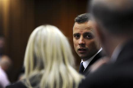 Olympic and Paralympic track star Oscar Pistorius speaks to members of his legal team during the fourth day of his trial for the murder of his girlfriend Reeva Steenkamp at the North Gauteng High Court in Pretoria