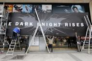 Employees remove promotional boards from the facade of a cinema where the French premiere of the latest Batman movie was supposed to take place on July 20. A special screening of the latest Batman movie in Paris will go ahead as planned Saturday after the deadly shooting spree at a US opening of the movie, the management of the cinema said Saturday