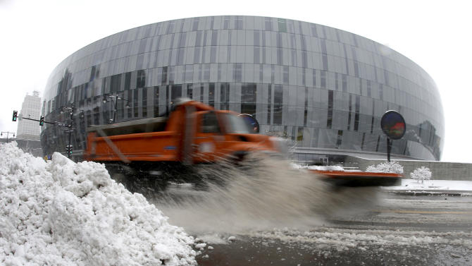 A snowplow clears the street in front of the Sprint Center, Sunday, March 24, 2013, in Kansas City, Mo. The city was preparing for the third round of the NCAA college basketball tournament at the arena after the region received 6-10 inches of snow overnight. (AP Photo/Charlie Riedel)