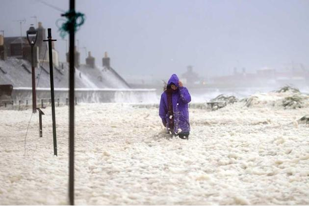 A woman makes her way through South Square in Aberdeen, that has been covered in a thick sea foam after flooding from the North sea as stormy weather affects the Scottish coast in September. Extreme w