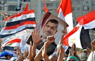 Muslim Brotherhood supporters hold a portrait of Mohamed Morsi during a rally outside the Rabaa al-Adawiya mosque in Cairo, on July 24, 2013. An Egyptian court has banned the Muslim Brotherhood from operating and ordered its assets seized, in the latest blow to the Islamist movement of Morsi