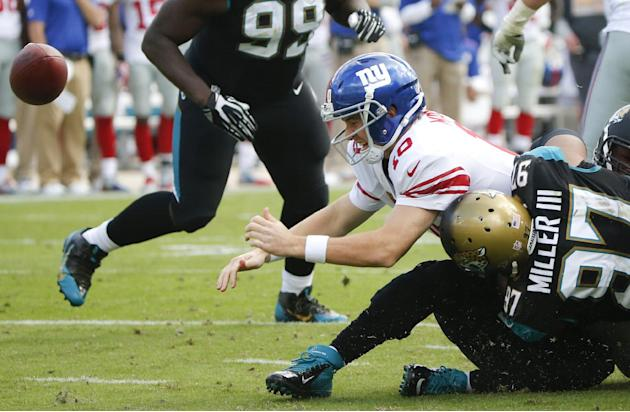 New York Giants quarterback Eli Manning (10) fumbles the ball as he is hit by Jacksonville Jaguars defensive tackle Roy Miller (97) during the second half of an NFL football game in Jacksonville, Fla.