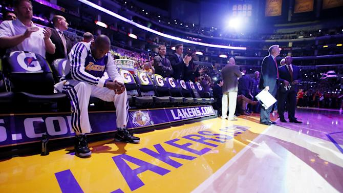 Los Angeles Lakers' Kobe Bryant sits on the bench, he is the last player to be introduced to the crowd, as head coach Mike D'Antoni, right, looks on before the NBA basketball game against the Toronto Raptors in Los Angeles, Sunday, Dec. 8, 2013. It was Bryant's first game back after a torn left Achilles tendon injury on April 12th