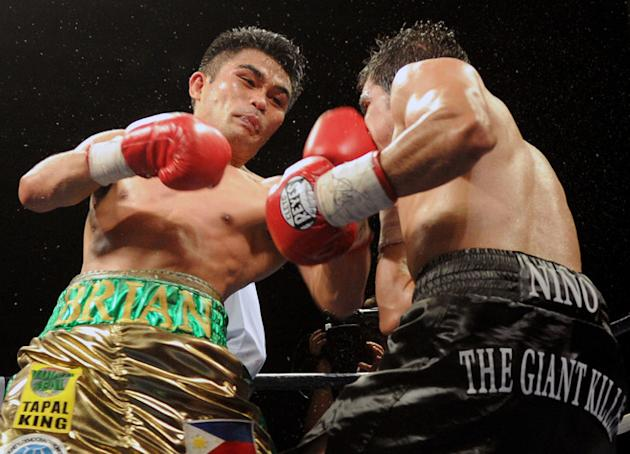Brian Viloria (L) of the Philippines punches Omar Nino Romero of Mexico during their WBO flyweight title bout in Manila on May 13, 2012. Viloria gained revenge over Mexico's Omar Nino Romero on May 13, winning by a technical knockout to retain his title in a hard-fought bout. TOPSHOTS AFP PHOTO / Jay DIRECTOJAY DIRECTO/AFP/GettyImages