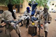 A picture taken on July 16, shows fighters of the Islamist group Movement for Oneness and Jihad in West Africa (MUJAO) sitting in the courtyard of the Islamist police station in Gao. Three European aid workers released in Mali after being kidnapped by the Al-Qaeda-linked group were freed in exchange for three Islamists, a negotiator said Thursday as they headed home