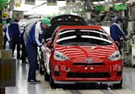 File photo shows workers making final checks on Toyota's compact hybrid vehicle AQUA on its assembly line in Tokyo. Japan logged a bigger-than-expected trade deficit of $6.5 bn in April as higher energy costs pushed up imports, the finance ministry said Wednesday