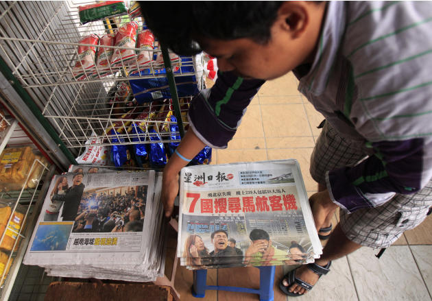A vendor prepares newspapers carrying a headline story and pictures of the missing Malaysian Airlines plane, in Shah Alam, outside Kuala Lumpur. An international fleet of planes and ships scoured the