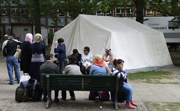 Refugees wait in the yard of the State Office of Health and Social Affairs in Berlin's Moabit district on July 31, 2015