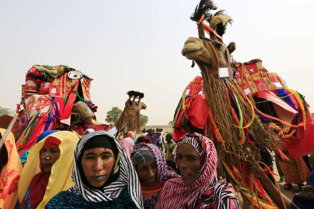 Tribal women stand next to camels during a re-election campaign rally by Sudanese President and NCP candidate Bashir in El-Ginana