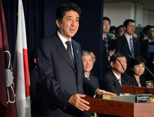 Japan's incoming Prime Minister and leader of Liberal Democratic Party (LDP) Shinzo Abe (L) speaks to the media as he names new LDP party executives at their headquarters in Tokyo on December 25, 2012. Abe is to be named as the country's new prime minister Wednesday, after he swept to power on a hawkish platform of getting tough on diplomacy while fixing the economy.