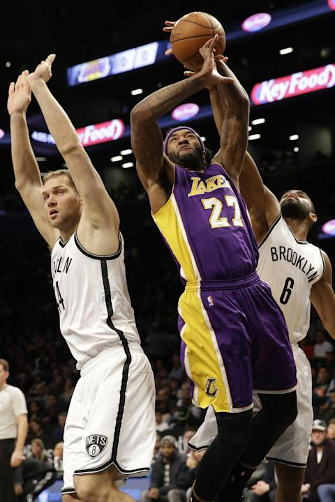 Los Angeles Lakers center Jordan Hill (27) goes to the basket against Brooklyn Nets guard Alan Anderson (6) and guard Bojan Bogdanovic (44) during the first half of an NBA basketball game, Sunday, Mar