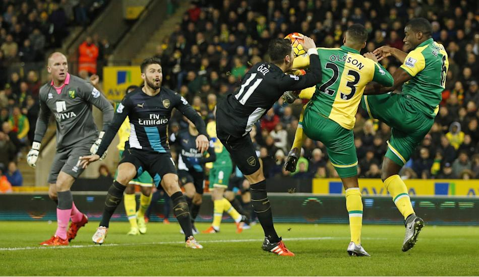 Norwich's Martin Olsson and Sebastien Bassong in action with Arsenal's Mesut Ozil