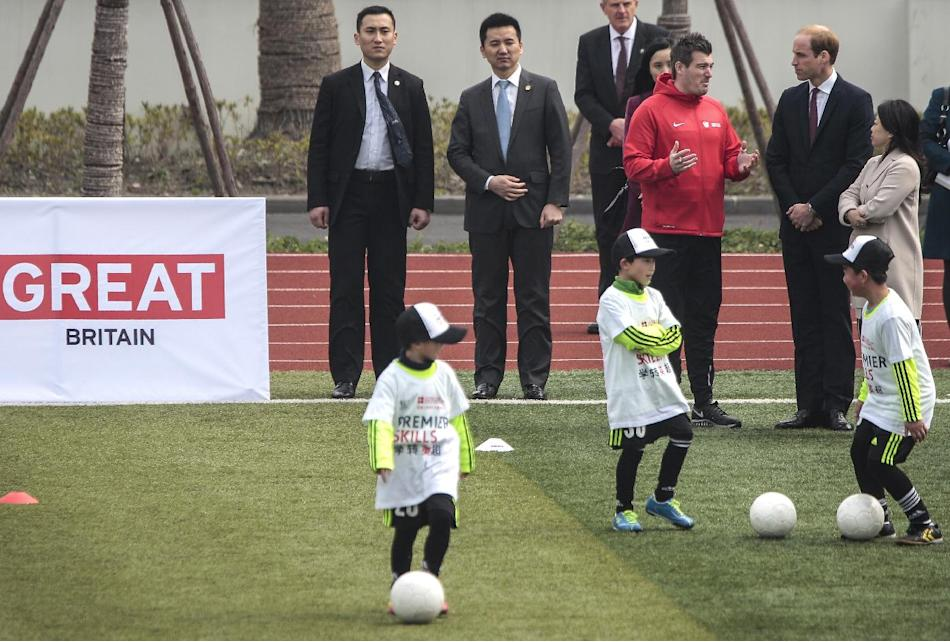 Britain's Prince William, second from right, chats with officials as he attends the Premier Skills football coaching event at Nanyang Secondary School in Shanghai, China Tuesday, March 3, 2015. Wi