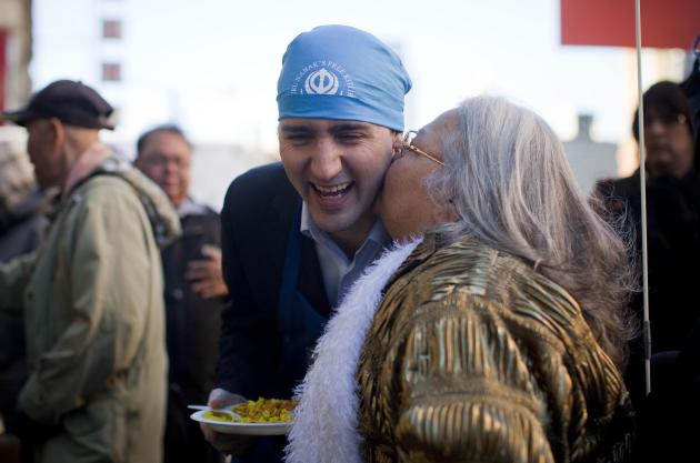 Leader of the Liberal Party of Canada MP Justin Trudeau gets a kiss from a woman in the downtown eastside neighbourhood in Vancouver.