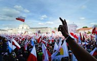 Demonstrators hold Polish national flags during an opposition rally in Warsaw