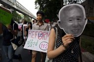 A Thai activist holds a sign calling for the reform of article number 112 in Thailand's Criminal Code as another one holds a mask representing imprisoned Ampon Tangnoppakul as they stage a march against the country's widely-criticised laws protecting the monarchy, in Bangkok, in December 2011
