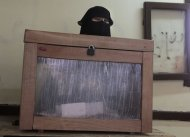 An Egyptian official wearing the Niqab stands next to a ballot box in Giza, Egypt, Wednesday, Dec. 14, 2011. Egyptians in nine provinces voted Wednesday in the second round of the first parliamentary elections since a popular uprising ousted President Hosni Mubarak in February. (AP Photo/Amr Nabil)