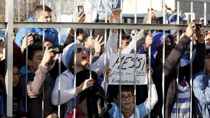 "An Argentina fan holds a sign that reads: ""Messi you are my idol, welcome"" as they watch the arrival of Argentina's soccer team in front of the hotel Radisson in Concepcion"