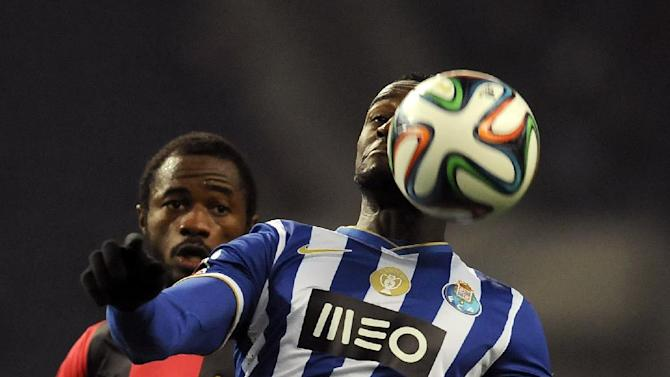 FC Porto's Jackson Martinez, right, from Colombia eyes the ball past Olhanense's Oumar Diakhite, from Senegal, in a Portuguese League soccer match at the Dragao Stadium in Porto, Portugal, Friday, Dec. 20, 2013. Jackson scored once in Porto's 4-0 victory