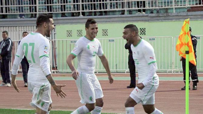 In this photo dated Wednesday, March 5, 2014, Algerian player, Soudani Hilal el Arabi, right, celebrates his opening goal with Saphir Taider and Liassine Cadamuro, left, during their international friendly match against Slovenia at Blida stadium, near the Algerian capital Algiers. Algeria defeated Slovenia 2-0