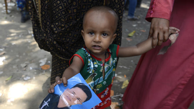 A young child holds a picture of his father who was missing since the collapse of the garment factory building, Thursday, May 2, 2013, in Savar, near Dhaka, Bangladesh. Rescuers found more bodies in the concrete debris of the collapsed garment factory building Thursday and authorities said it may take another five days to clear the rubble. In addition to the 430 confirmed dead, police report another 149 people are still missing in what has become the worst disaster for Bangladesh's $20 billion-a-year garment industry that supplies global retailers.(AP Photo/Ismail Ferdous)