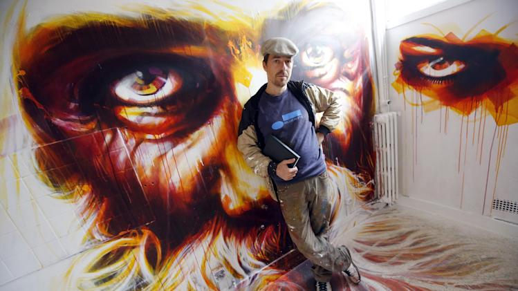 French artist Dan23 poses front of his paintings in a social housing tower converted into a temporary street art exhibition in Paris, France, Tuesday, Oct. 8, 2013. Condemned apartments never looked so good _ and only rarely has graffiti met such an enthusiastic welcome. More than 80 artists were given free run of a rundown building that is doomed to destruction in 8 days. The line wraps around the block every day to see the apartments, each of which is its own art installation. (AP Photo/Francois Mori)