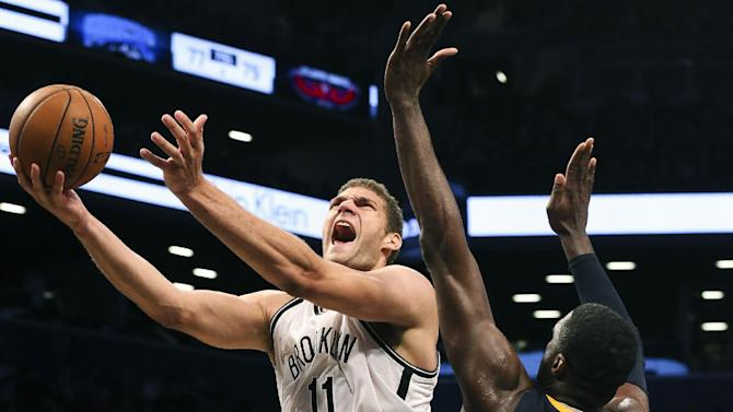 Brooklyn Nets center Brook Lopez (11) drives to the net against Indiana Pacers center Roy Hibbert (55)  during the fourth quarter of a NBA basketball game, Saturday, Nov. 9, 2013, at the Barclays Center in New York. The Indiana Pacers defeated the Brooklyn Nets, 96-91
