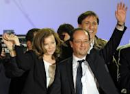 France's Socialist Party (PS) newly elected president Francois Hollande and his companion Valerie Trierweiler wave on stage at the Place de la Bastille after the announcement of the first official results of the French presidential second round