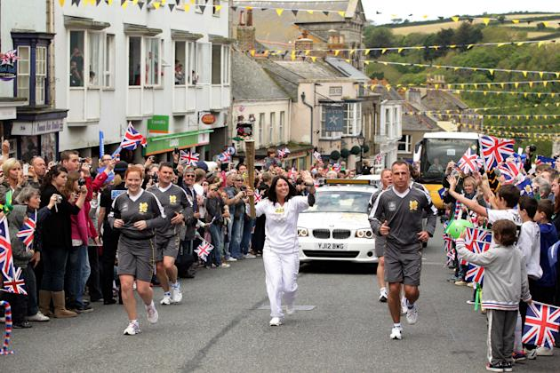 This photograph issued by  LOCOG shows torchbearer Nicole Martin carrying the Olympic torch during the leg of the torch relay between the villages of Rosudgeon and Helston in south west England Saturd