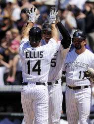 Colorado Rockies' Mark Ellis (14) and Carlos Gonzalez celebrate Ellis' home run in the fifth inning of an interleague baseball game against the Kansas City Royals in Denver on Sunday, July 3, 2011. The Royals won 16-8. (AP Photo/Chris Schneider)
