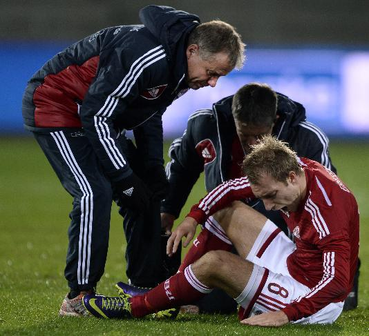 Denmark's Christian Eriksen, right, sits on the pitch after an injury during the international soccer match in Herning, Denmark, Friday Nov. 15, 2013