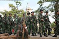 Indonesian soldiers surround a Papuan tribal warrior armed with bow and arrow on June 18. Two tribesmen were killed when rival groups armed with bows and arrows clashed in Indonesia's restive Papua province on Monday, police said