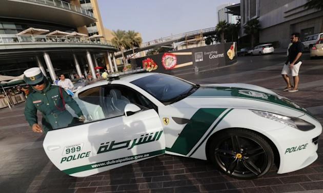 An Emirati female police officer gets out of a Ferrari police vehicle on April 25, 2013 in the Gulf emirate of Dubai. Dubai police showed off a new Ferrari they will use to patrol the city state, hot