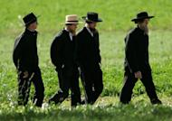 Amish men walk to a funeral for a victim of the Amish schoolhouse shootings, on October 5, 2006, in Nickel Mines, Pennsylvania. The leader of a breakaway Amish group who ordered his followers to chop off his rivals' beards was sentenced Friday to 15 years in prison after being convicted of hate crimes