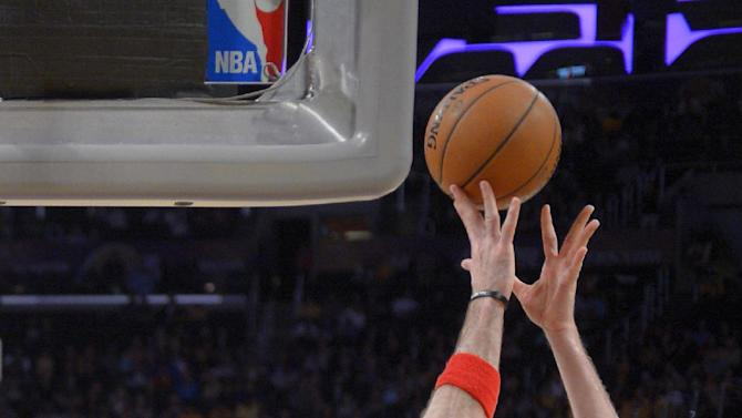 Los Angeles Lakers center Pau Gasol, of Spain,, right, puts up a shot as Washington Wizards center Marcin Gortat, of Poland, defends during the second half of an NBA basketball game, Friday, March 21, 2014, in Los Angeles. The Wizards won 117-107