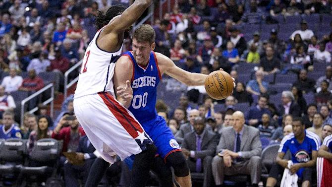 Philadelphia 76ers center Spencer Hawes (00) drives past Washington Wizards forward Nene during the first half of an NBA basketball game on Monday, Jan. 20, 2014 in Washington