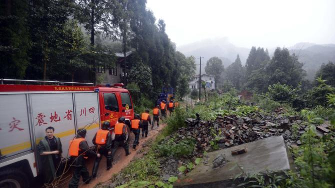 Rescue workers head to the site of a massive landslide on Wuxiangang Hill of Sanxi village in Dujiangyan city in southwestern China's Sichuan province Wednesday, July 10, 2013. Flooding in western China, the worst in 50 years for some areas, triggered a landslide Wednesday that buried about 30 people, trapped hundreds in a highway tunnel and destroyed a high-profile memorial to a devastating 2008 earthquake. (AP Photo) CHINA OUT