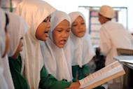 This file photo shows Muslim students reading books at an elementary school in Manila, in 2008. A Catholic-run school in the southern Philippines has caused controversy by banning Muslim students from wearing the hijab headscarf