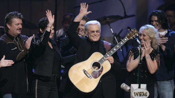 "FILE - In this Sept. 12, 2006 file photo, Country music legend George Jones waves to the crowd during his 75th birthday celebration at the Grand Ole Opry House in Nashville, Tenn., on Tuesday, Sept. 12, 2006. From left are Joe Diffie; Jones' wife, Nancy; Craig Morgan; Jones; Tanya Tucker; and Joe Nichols.   Jones, the peerless, hard-living country singer who recorded dozens of hits about good times and regrets and peaked with the heartbreaking classic ""He Stopped Loving Her Today,"" has died. He was 81. Jones died Friday, April 26, 2013 at Vanderbilt University Medical Center in Nashville after being hospitalized with fever and irregular blood pressure, according to his publicist Kirt Webster.(AP Photo/Mark Humphrey, file)"