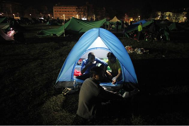 A Nepalese man has food inside a tent as people stay on open ground from fears of earthquake tremors in Kathmandu, Nepal, Monday, April 27, 2015. A strong magnitude earthquake shook Nepal's capital an