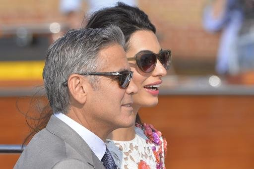 US actor George Clooney and his wife Amal Alamuddin stand on a taxi boat on September 28, 2014 in Venice, Italy