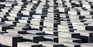 A man walks past concrete steles of the Monument for the Murdered Jews of Europe in Berlin in January. Residents of one Berlin apartment building have tracked down the names and fates of the Jewish people who once lived there and put up a plaque to remember them individually