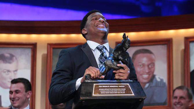 In this photo provided by the Heisman Trust, Florida State quarterback Jameis Winston hoists the Heisman Trophy after being named college football's best player during the Heisman Trophy presentation in New York on Saturday, Dec. 14, 2013